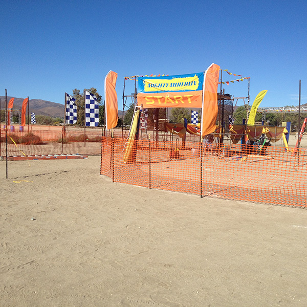 At the Acton Movie Ranch, there are various mud run obstacles set up on flat, graded terrain.