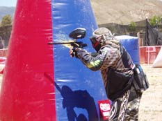 Paintball USA - Player aiming next to cover