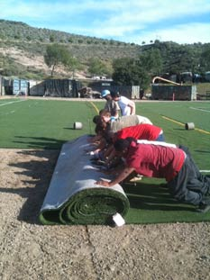 Paintball USA - Rolling out turf for field